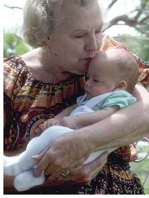 Grandma kissing baby.
